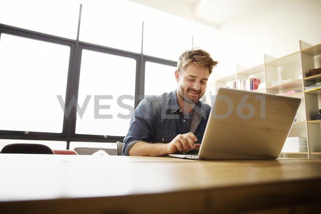 Happy man using laptop at table - CAVF00395
