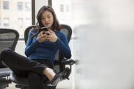 Woman text messaging while sitting on chair in office - CAVF00401