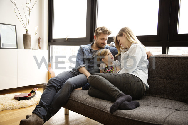 Family sitting on couch in living room - CAVF00416