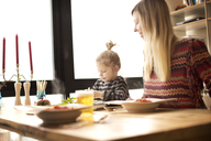 Mother looking at girl having food at table - CAVF00422