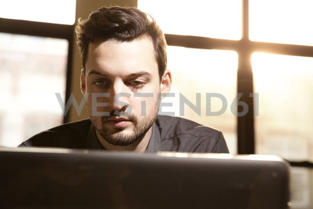 Businessman working on laptop in creative office - CAVF00446