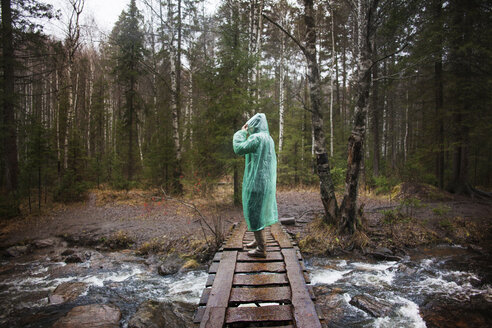 Man wearing raincoat while standing on footbridge in forest - CAVF00590