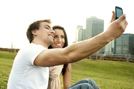 Happy couple taking selfie on lawn in city - CAVF00614