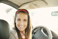 Portrait of smiling woman sitting in car on sunny day - CAVF00620