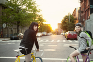 Portrait of friends with bicycles on city street during sunset - CAVF00626