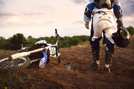 Low section of dirt biker standing on field - CAVF00653
