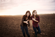 Female friends laughing at farm against sky during sunrise - CAVF00731