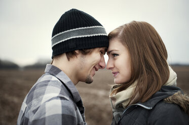 Close-up of smiling young couple looking at each other - CAVF00743
