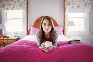 Portrait of confident woman holding coffee mug while lying on bed at home - CAVF00752