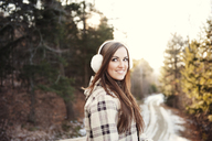 Happy woman wearing ear muff while standing on footpath during winter - CAVF00764