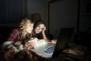 Friends using laptop while lying on bed at home - CAVF00767