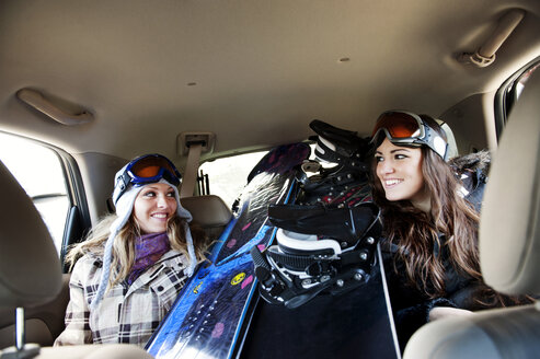 Happy female skiers sitting by snowboards in car - CAVF00770