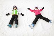 Siblings making snow angel on field during winter - CAVF00773