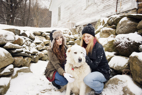 Happy female friends with dog by stones in winter - CAVF00779