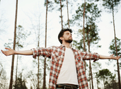 Man with arms outstretched standing against trees in forest - CAVF00791