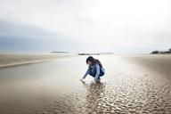 Woman crouching on beach against cloudy sky - CAVF00818