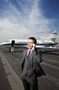 Businessman talking on phone while standing against corporate jet on runway - CAVF00860