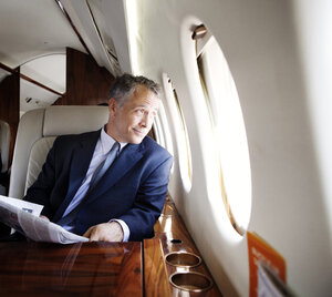 Smiling businessman holding newspaper while looking through corporate jet window - CAVF00863