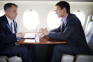 Businessmen discussing in meeting while traveling in corporate jet - CAVF00869