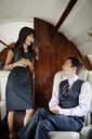 Happy businessman looking at female colleague while traveling in corporate jet - CAVF00872