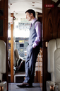 Profile view of thoughtful businessman standing in corporate jet - CAVF00875
