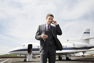 Businessman communicating on phone while standing against corporate jet on runway - CAVF00878