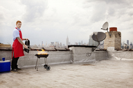 Portrait of man preparing food while on barbecue at building terrace against sky - CAVF00908