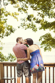 Rear view of parents kissing son while standing by railing against lake - CAVF00950
