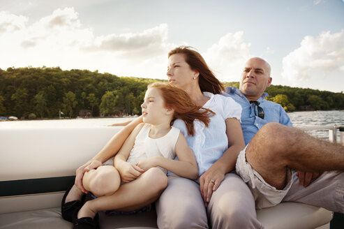 Girl relaxing with parents while traveling in boat on lake - CAVF00973