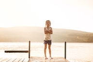 Portrait of girl with arms crossed standing on jetty over lake against clear sky during sunset - CAVF00979
