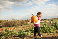 Happy girl holding pumpkin while standing on field against sky on sunny day - CAVF01006