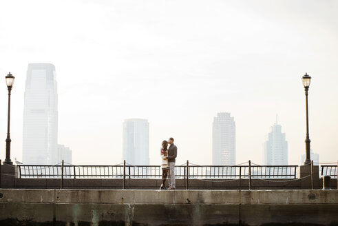 Young couple standing on footbridge against clear sky - CAVF01024