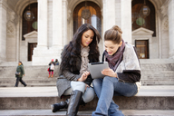 Young female friends looking at digital tablet while sitting on steps - CAVF01027