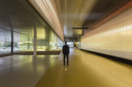 Businessman standing in illuminated modern office lobby corridor - CAIF04600