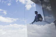 Businessman on modern balcony looking out window at blue sky and clouds - CAIF04603