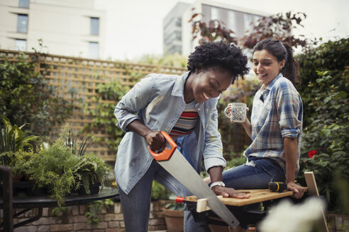 Women drinking coffee and cutting wood with saw on patio - CAIF04675