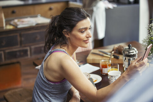 Young woman texting with smart phone at breakfast table - CAIF04678