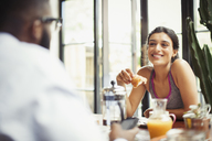 Smiling couple eating breakfast - CAIF04690