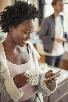 Smiling woman drinking coffee, texting with smart phone - CAIF04702