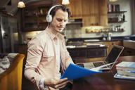 Man with headphones working at laptop, reading paperwork in kitchen - CAIF04720