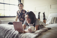 Smiling couple relaxing, drinking coffee and using digital tablet on bed - CAIF04726