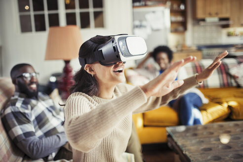 Woman gesturing, using virtual reality simulator glasses in living room - CAIF04729