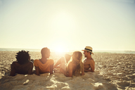 Young couples laying, relaxing on sunny summer beach - CAIF04795