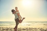 Playful boyfriend lifting girlfriend on sunny summer ocean beach - CAIF04801