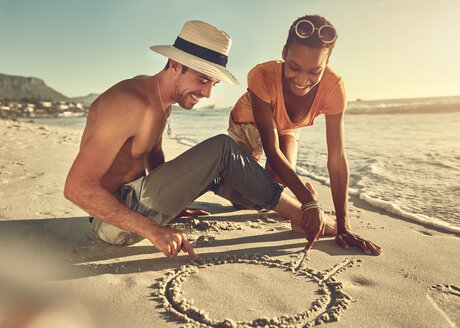 Young couple drawing in sand on sunny summer ocean beach - CAIF04816
