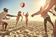 Playful young friends playing with beach ball on sunny summer beach - CAIF04822