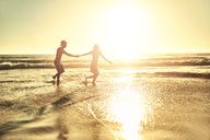 Young couple holding hands, walking in sunny summer sunset ocean beach surf - CAIF04837