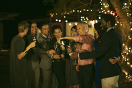 Friends celebrating with champagne at party - CAIF04847