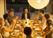 Friends applauding man at dinner party - CAIF04865