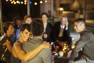 Couple hugging at party - CAIF04880